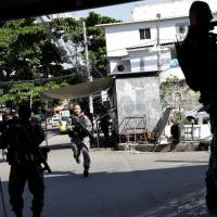Police take up positions during an operation in Alemao slum complex, after violent clashes between policemen and drug dealers in Rio de Janeiro Thursday. | REUTERS