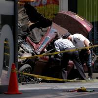 Police investigate the vehicle that drove onto sidewalk and struck pedestrians in Times Square in New York Thursday. | REUTERS