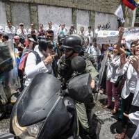 Doctors chant slogans in front of a line of National Guard personnel in riot gear during a demonstration against the shortage in medicines and in rejection of the government of President Nicolas Maduro, in Caracas on Wednesday. | AFP-JIJI