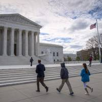 Visitors arrive at the Supreme Court in Washingtonlast month. The Supreme Court on Monday rejected an appeal to reinstate North Carolina's voter identification law that a lower court said targeted African-Americans 'with almost surgical precision.' | AP