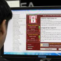 Staffers monitor the spread of ransomware cyberattacks at the Korea Internet and Security Agency in Seoul on Monday. | AFP-JIJI