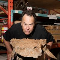 Actor Dan Aykroyd poses in the Royal Ontario Museum's paleontology collections room with fossils of Zuul crurivastator, a new species of armored dinosaur named after the beast Zuul from the film 'Ghostbusters,' in Toronto on April 21.   REUTERS