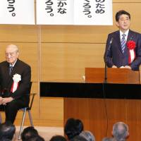 Prime Minister Shinzo Abe speaks at a gathering in Tokyo Monday of a cross-party league of lawmakers who favor amending the Constitution, alongside former Prime Minister Yasuhiro Nakasone. | KYODO