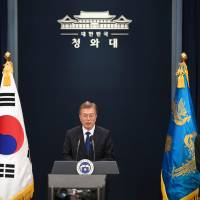 South Korea's new President Moon Jae-in (left) speaks as prime ministerial nominee Lee Nak-yeon listens during a news conference at the presidential Blue House in Seoul on Wednesday. | AFP-JIJI