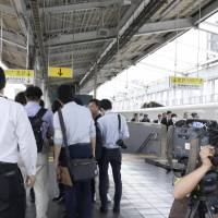 Reporters gather Friday at a platform in JR Okayama Station, where an elderly man was arrested for allegedly starting a fire inside a shinkansen. | KYODO