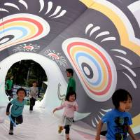Children walk through a 25-meter long 'koinobori,' or carp-shaped streamer, in the Roppongi area of Tokyo's Minato Ward on Thursday, one day before Children's Day of May 5. Koinobri is traditionally flown to wish for good health and happiness of children. | SATOKO KAWASAKI