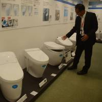 Ikuya Idota of Lixil Group Corp. shows generations of toilets with built-in spray wash displayed at the firm's factory in Tokoname, Aichi Prefecture. | CHUNICHI SHIMBUN