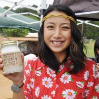 Ai Fujiwara shows a bottle of coconut oil in Kobe that was imported from Kapoposang Island in Indonesia. | AI FUJIWARA / VIA KYODO
