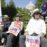Protesters rally near the Diet building on Friday. | KYODO