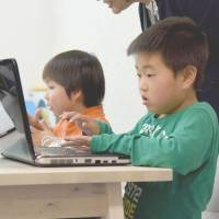 Eita Ide (right) studies computer programming at Kid's Tech, a newly opened cram school catering to the needs of children with developmental disabilities in Tokyo's Ota Ward in mid-April. | SATOKO KAWASAKI
