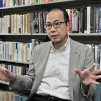 Keio University professor Eisaku Ide explains his proposed economic policy which he hopes will serve as a counterweight to the growth-driven Abenomics, during an interview in Tokyo on April 19. | YOSHIAKI MIURA