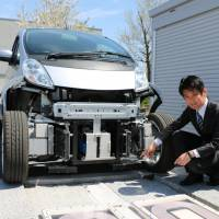 Hiroshi Fujimoto, an associate professor at the University of Tokyo, shows off an electric vehicle capable of being charged while in motion, as well as the in-road charging infrastructure, at the university's Kashiwa campus in Chiba Prefecture last month. | KYODO