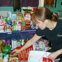 An employee of fitness club Curves Japan in Tokyo stocks food donated by the club's members. The franchise has been promoting food drives since 2007. | KYODO