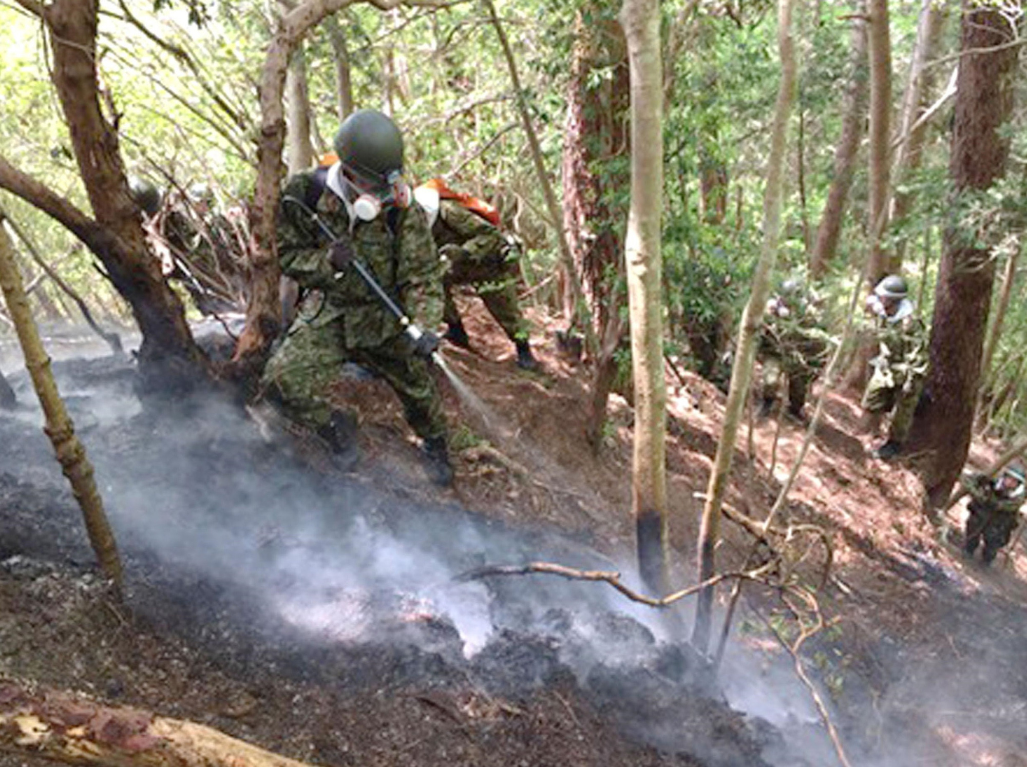 Ground Self-Defense Force personnel work on putting out fire in a forest in Namie, Fukushima Prefecture on May 4. | GSDF/VIA KYODO