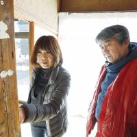 Hidenobu Fukumoto (right), head of a group that produces picture-story shows, visits the home of Yoko Oka in Namie, Fukushima Prefecture, in January. Namie was a restricted zone until the government lifted an evacuation order in March. | KYODO