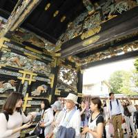 Tourists walk through the Karamon gate of Nishi Honganji Temple in Kyoto on Sunday. The gate, a national treasure, was opened for the first time in 34 years. | KYODO
