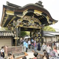Tourists walk through the Karamon gate of the Nishi Honganji Temple in Kyoto on Sunday. | KYODO