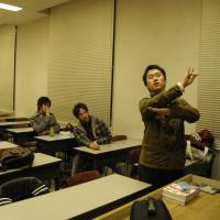 Junto Ohki practices sign language with members of a club he set up while he was a student at Keio University.   JUNTO OHKI