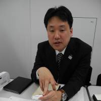 Daiki Shimamura, an ALSOK official, says this thumb-size electronic device developed by the company can help find missing people with dementia quickly. | KYODO