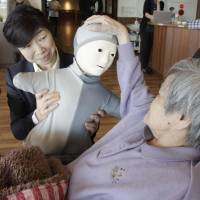 An elderly woman at a nursing home in Natori, Miyagi Prefecture, touches a humanoid robot that is remotely controlled by a staff member with a PC in the background. | KYODO