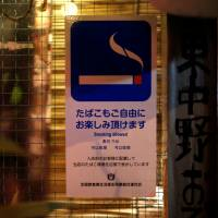 A sign reading 'smoking allowed' is displayed outside an 'izakaya' (pub) in Tokyo in March. | REUTERS