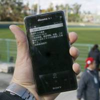 Information from the J-Alert warning system is displayed on a smartphone in Ginowan, Okinawa Prefecture, during a test on Sunday. | KYODO