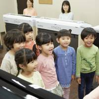 Children listen to a teacher's piano performance during a music lesson at a Yamaha Music Foundation school. Yamaha has 3,300 outlets across Japan. | YAMAHA MUSIC FOUNDATION