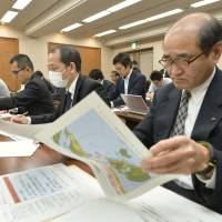 Prefectural representatives peruse documents during a meeting in Tokyo on April 21 as they listen to the central government offer guidance on how to respond if North Korea launches a missile. | KYODO