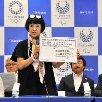 Yoshiko Ikoma, vice chairwoman of the panel in charge of mascot selection for the 2020 Tokyo Olympic Games, holds a sign at a news conference in Tokyo on Monday. | YOSHIAKI MIURA