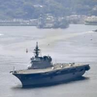The Izumo, a Maritime Self-Defense Force vessel, leaves Yokosuka naval base on Monday to protect a U.S. supply ship. | KYODO