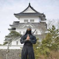 A man dressed as a ninja poses near Ueno Castle in Iga, Mie Prefecture. | CULTURAL AFFAIRS AGENCY / VIA KYODO