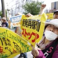 Protesters rally against the rebooting of the Takahama No. 4 reactor outside Kansai Electric Power Co.'s headquarters in Osaka on May 17. | KYODO