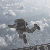 An airman participates in a parachuting drill above Kadena Air Base in Okinawa on April 24. A similar drill was conducted on Wednesday. | U.S. AIR FORCE