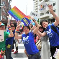 Marchers carry the rainbow flag during the annual Tokyo Rainbow Pride event held in the Shibuya district of central Tokyo on Sunday. This year's theme was 'change,' a call to respect everyone as individuals, regardless of their sexuality. | YOSHIAKI MIURA