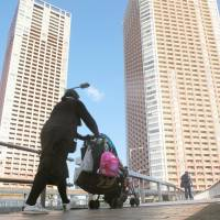 A woman pushes a stroller near a high-rise apartment complex in Minato Ward, Tokyo, in April. | KYODO