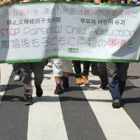 A group of about 30 parents whose children were abducted by spouses take part in a demonstration in Taito Ward, Tokyo, on Friday, to lobby for the inclusion of joint custody rights in the Japanese legal system. | DAISUKE KIKUCHI