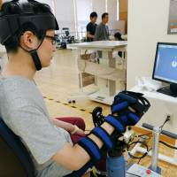 A patient uses a robotic arm made by Teijin Pharma, the health care business unit of synthetic-fibers maker Teijin Ltd., at Kansai Rehabilitation Hospital in Toyonaka, Osaka Prefecture. | KYODO