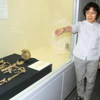 A human skeleton believed to be about 27,000 years old is displayed at a cultural facility in the town of Nishihara in Okinawa on Friday. | KYODO