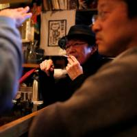 A man smokes at a pub in Tokyo in March. Many ruling Liberal Democratic Party lawmakers, supported by tobacco farmers and retailers, are opposed to a health ministry-drafted bill to ban indoor smoking. | REUTERS
