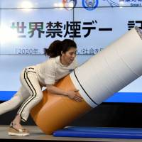 Three-time Olympic women's wrestling gold medalist Saori Yoshida tackles a cushion shaped like a cigarette during a World No Tobacco Day event in the Akasaka district in Tokyo on Wednesday. The event was aimed at protecting people's health from smoking and passive smoking. | SATOKO KAWASAKI