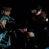 Members of the Hado team called Slamdiva, Piyohina (left), Junpei Sasaki (center) and Rimiko Sakihama, pose for a photograph wearing head-mounted displays and armband sensors in Tokyo in March. | REUTERS