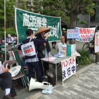 Activists gather in front of Kansai Electric Power Co.'s headquarters in Osaka on Wednesday to protest the restart of the Takahama No. 4 reactor, which is back online after more than 14 months. | ERIC JOHNSTON