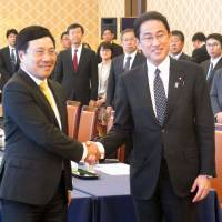 Vietnamese Deputy Prime Minister Pham Binh Minh (left) is greeted by Foreign Minister Fumio Kishida ahead of their talks in Tokyo on Monday. | KYODO