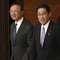 China's State Councilor Yang Jiechi (left) is escorted by Foreign Minister Fumio Kishida at their meeting at the Iikura Guesthouse in Tokyo on Tuesday. | AP