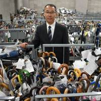 Shoji Okubo, head of the Metropolitan Police Department's lost and found center in Bunkyo Ward, stands with umbrellas that are waiting to be claimed by their owner. | SATOKO KAWASAKI