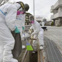 Ground Self-Defense Force members decontaminate areas tainted with radioactive substances in Iitate, Fukushima Prefecture, in December 2011.   KYODO