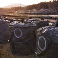 Bags filled with contaminated waste sit in a field in the village of Iitate, Fukushima Prefecture, in March 2016.   KYODO