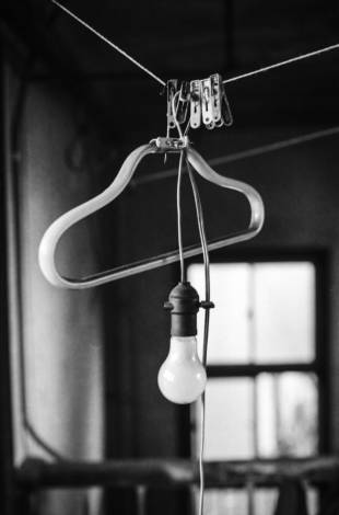 A light bulb hangs on a washing line in a hastily abandoned apartment.