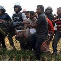Bangladeshi police officials carry an injured fireman during a raid on a Islamic militant  hideout in Rajshahi on May 11. | AFP-JIJI