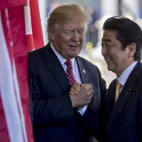 U.S. President Donald Trump greets Prime Minister Shinzo Abe as he arrives at the White House on Feb. 10. Abe has delivered much more on longstanding demands by the U.S. than all of his predecessors combined, shifting Japan toward a beefed-up military role in the alliance. | BLOOMBERG